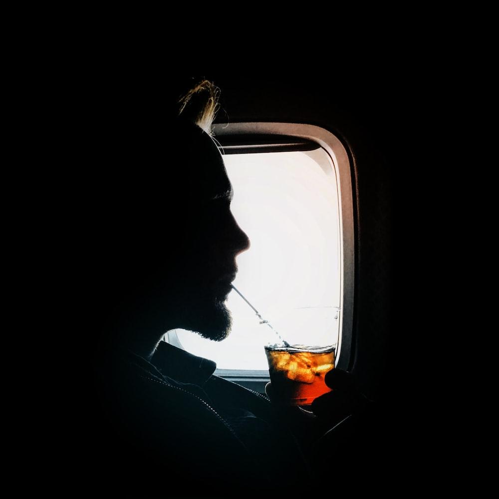 man sipping drink beside window