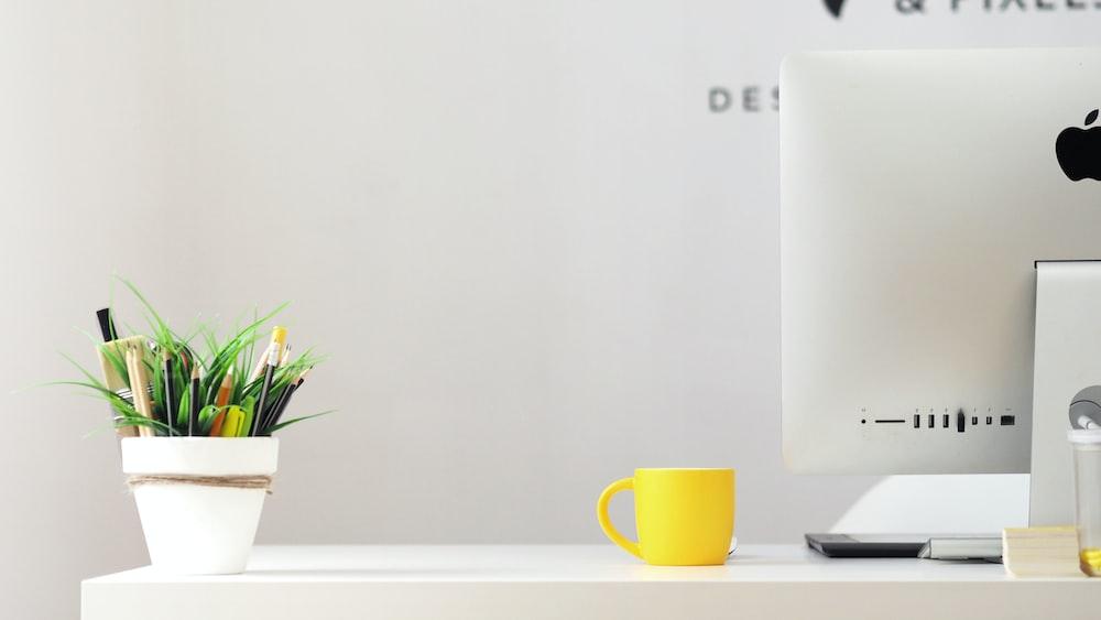 yellow ceramic mug beside gray aluminum iMac
