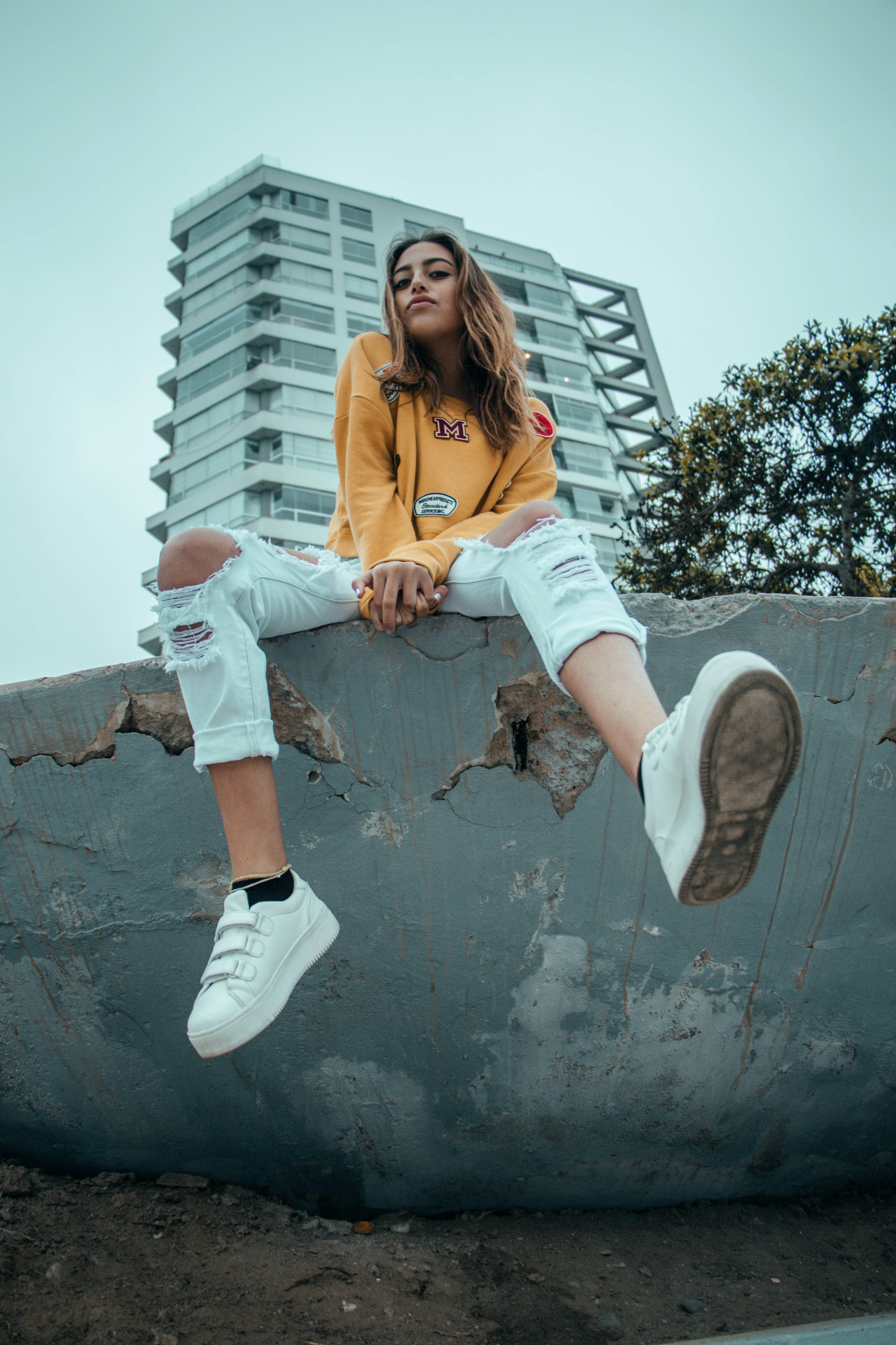 woman wearing orange sweater and distressed white denim jeans sitting on gray concrete wall at daytime