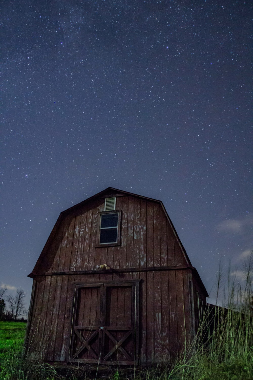 brown wooden barn under starry sky