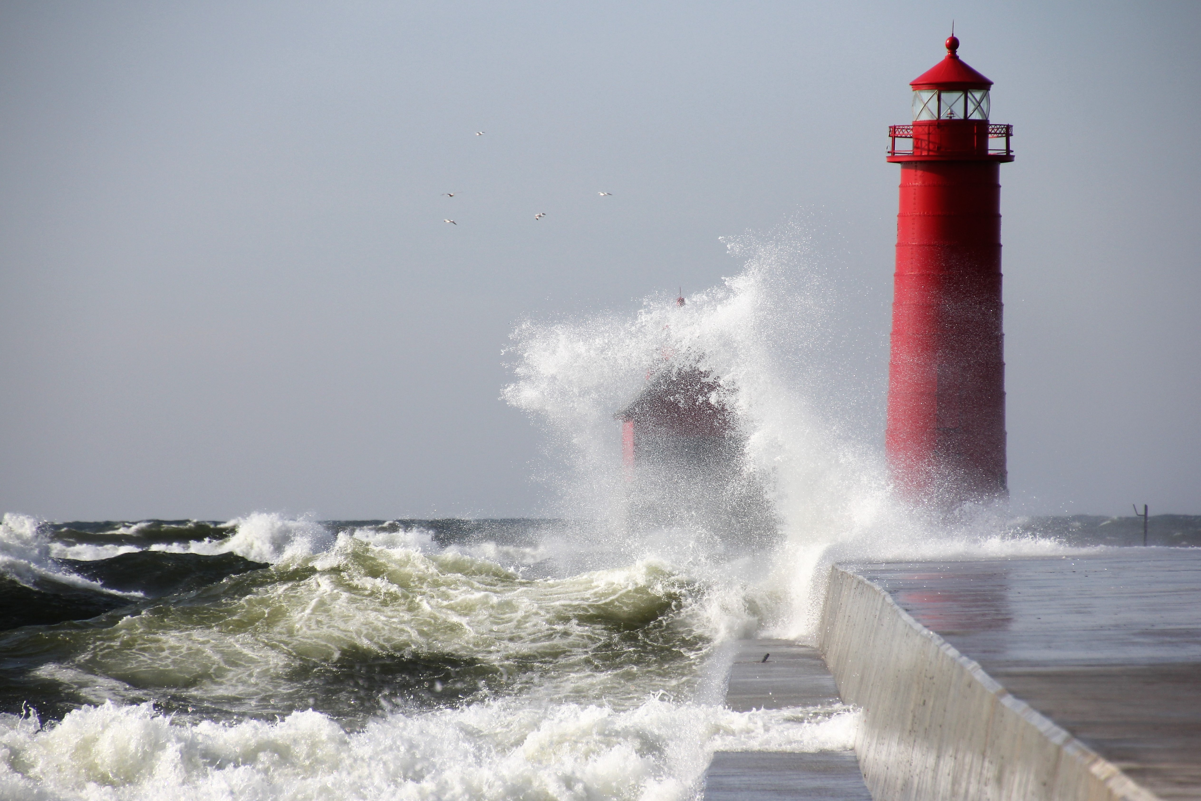 waves crushing the red lighthouse under gray sky during daytime