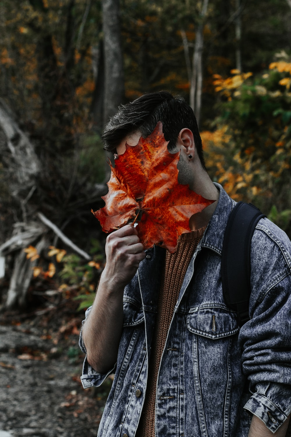 man covering face with leaf