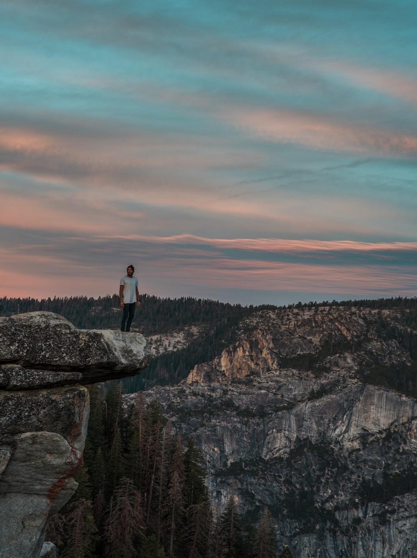 man standing on cliff near mountain