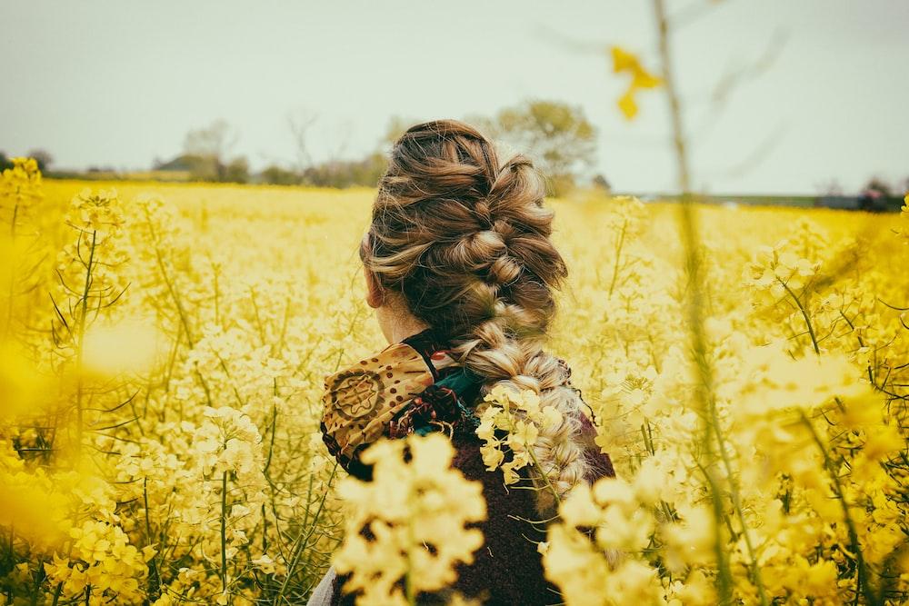 woman sitting beside yellow flowers