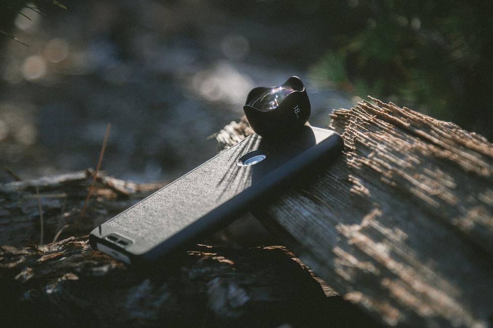 black smartphone with camera lens on tree log