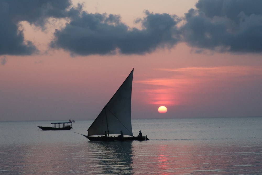 photograph of sail boat on calm body of water during golden hour