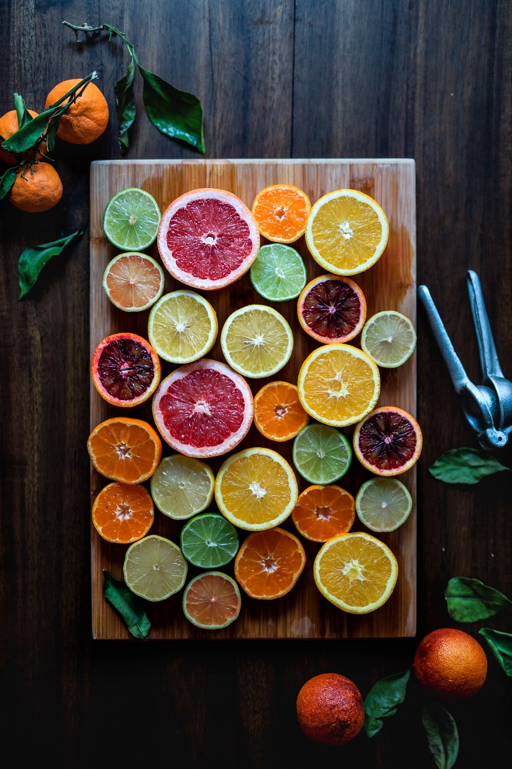 assorted sliced citrus fruits on brown wooden chopping board