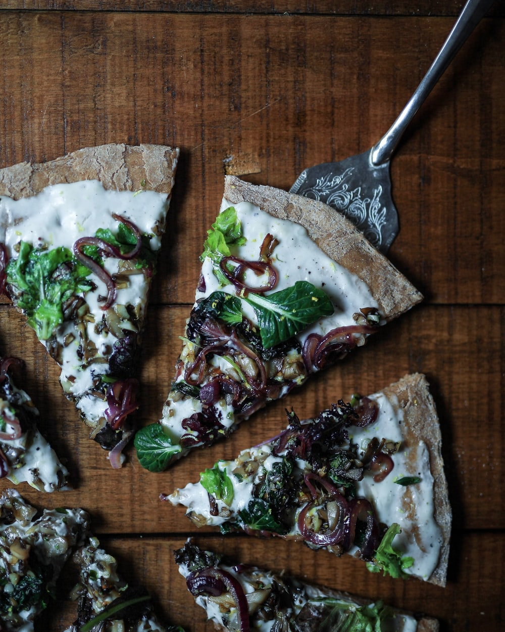 sliced pizza with leafy vegetable toppings