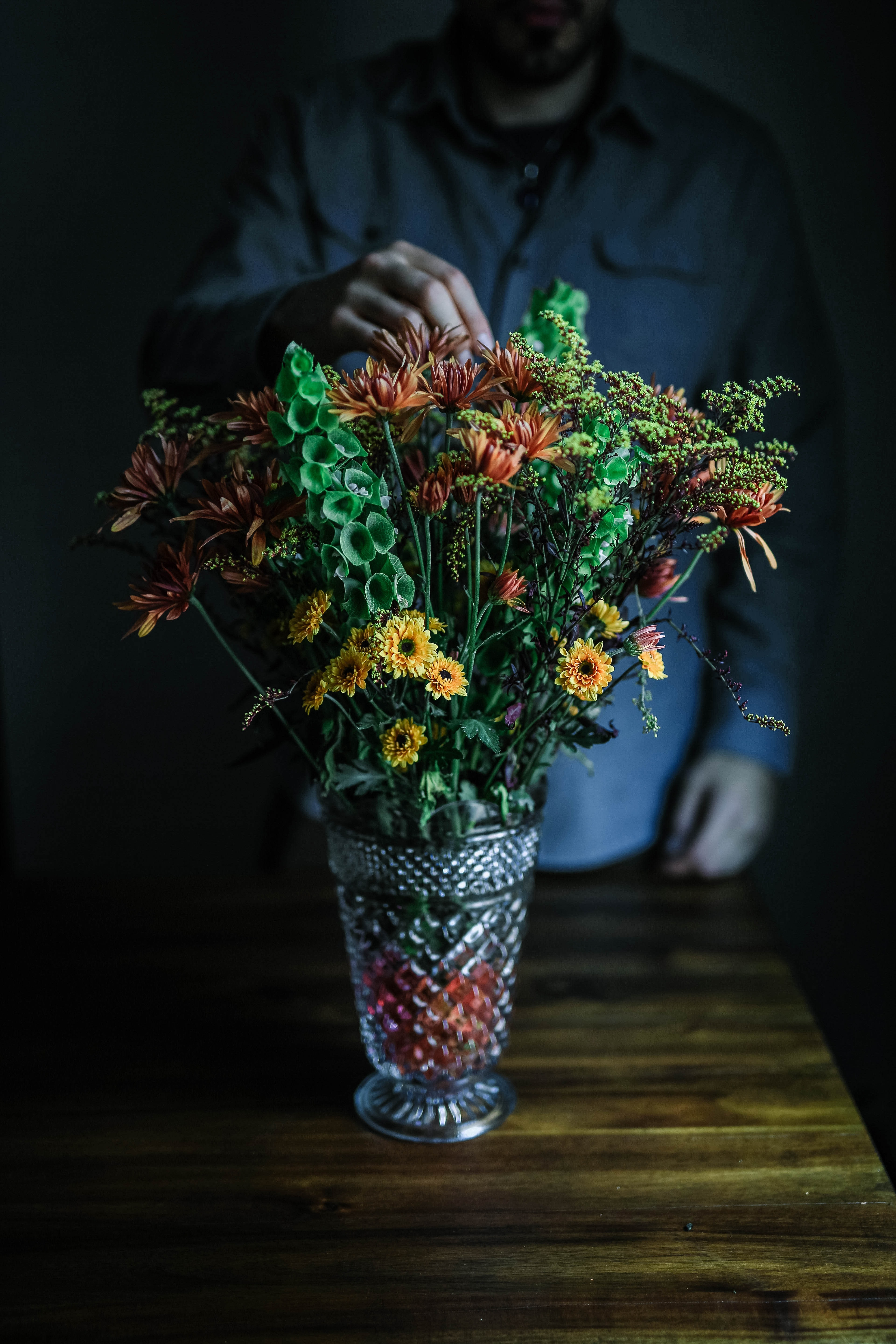 person touching vase of flowers