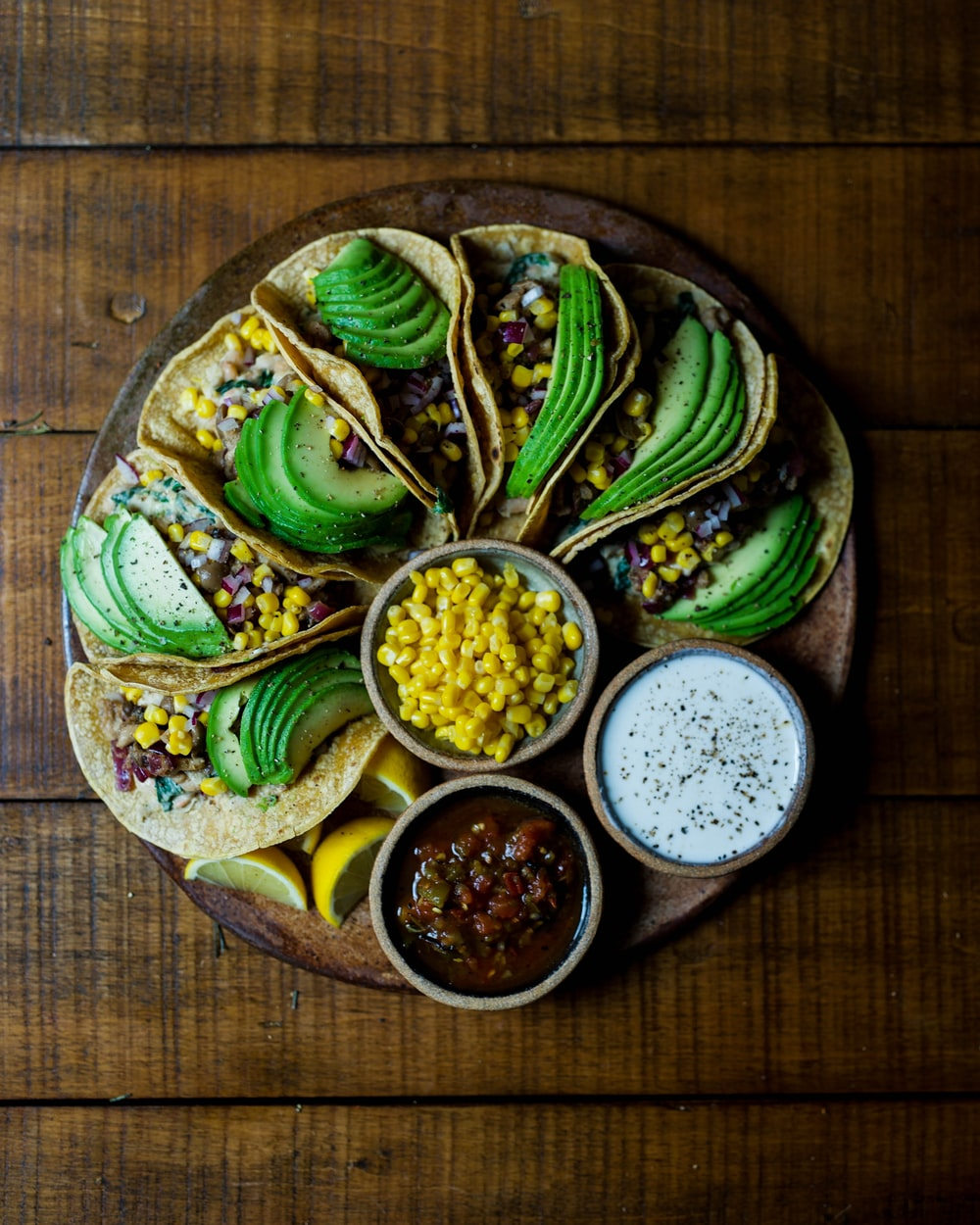 Photo Via: https://unsplash.com/photos/J04BD4ysoh8, avocado tacos on a healthy platter for presentation with corn and salsas.