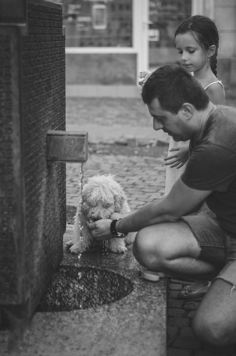 man kneeling beside girl feeding dog in grayscale photograpy