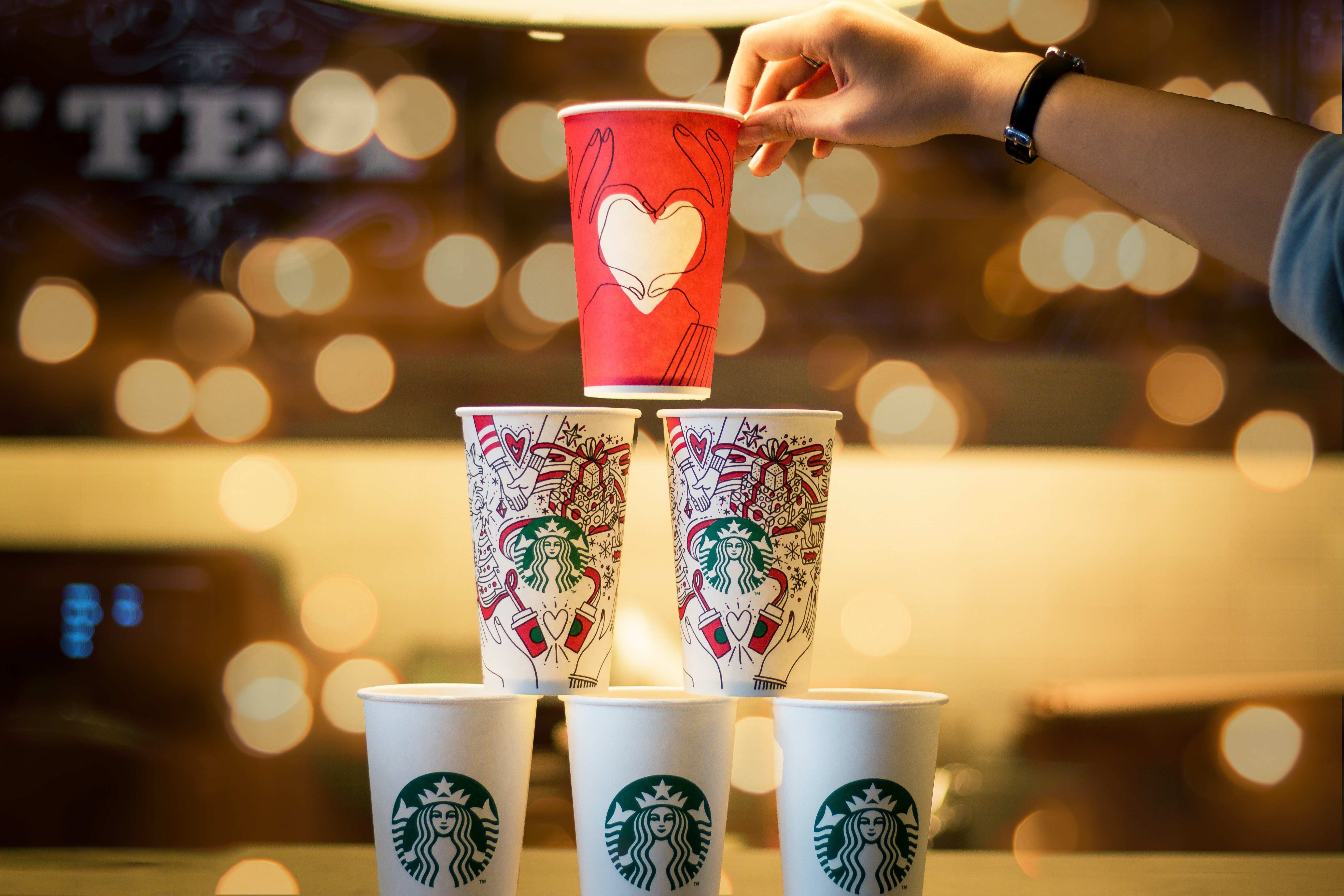 person stacking five assorted-color Starbucks cups