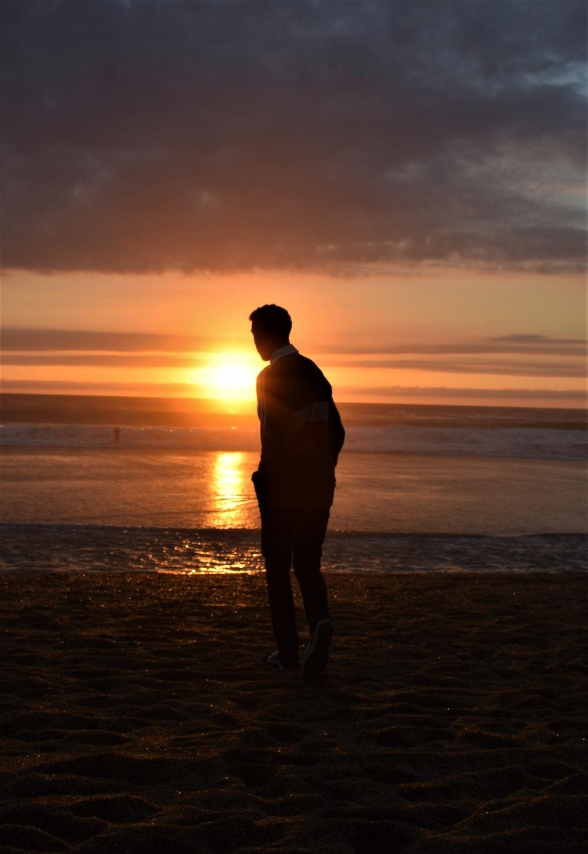 man walking seashore