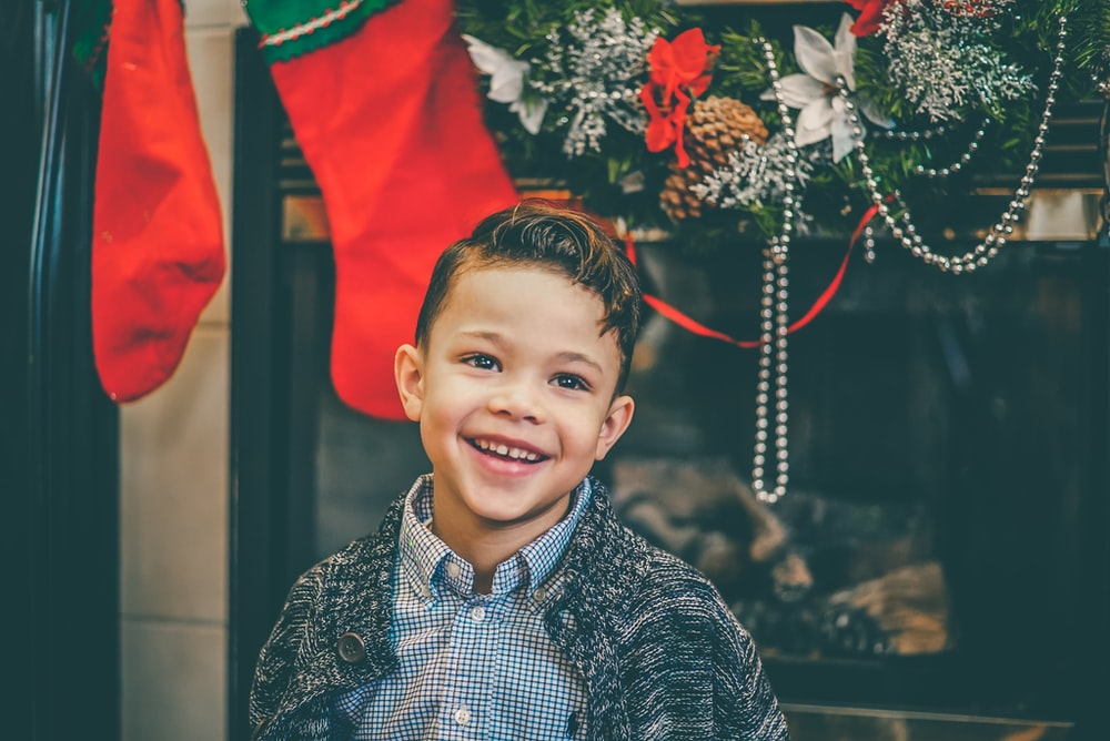 smiling boy in gray inner shirt and gray cardigan standing by fireplace with decors