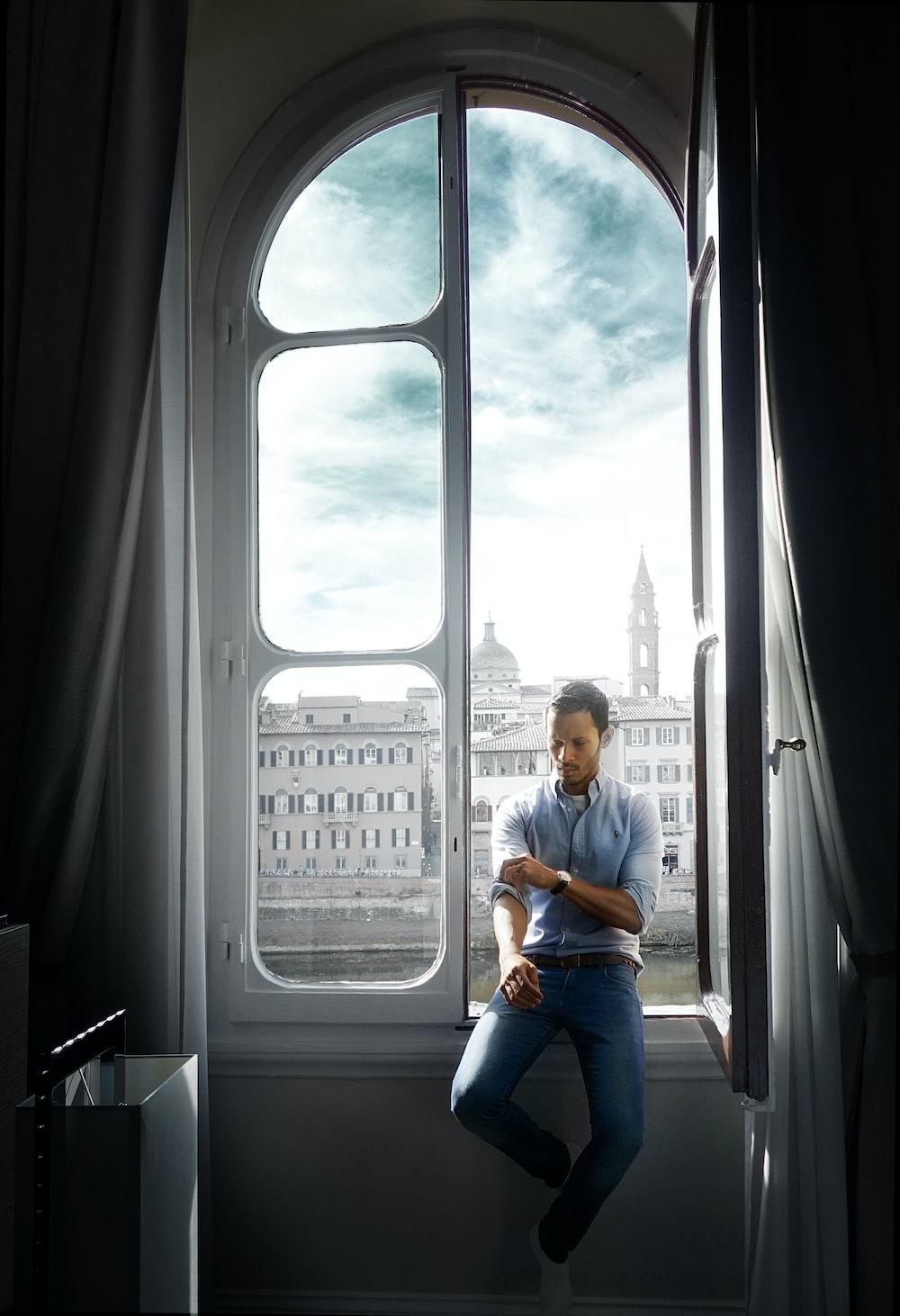 man sitting on window during daytime
