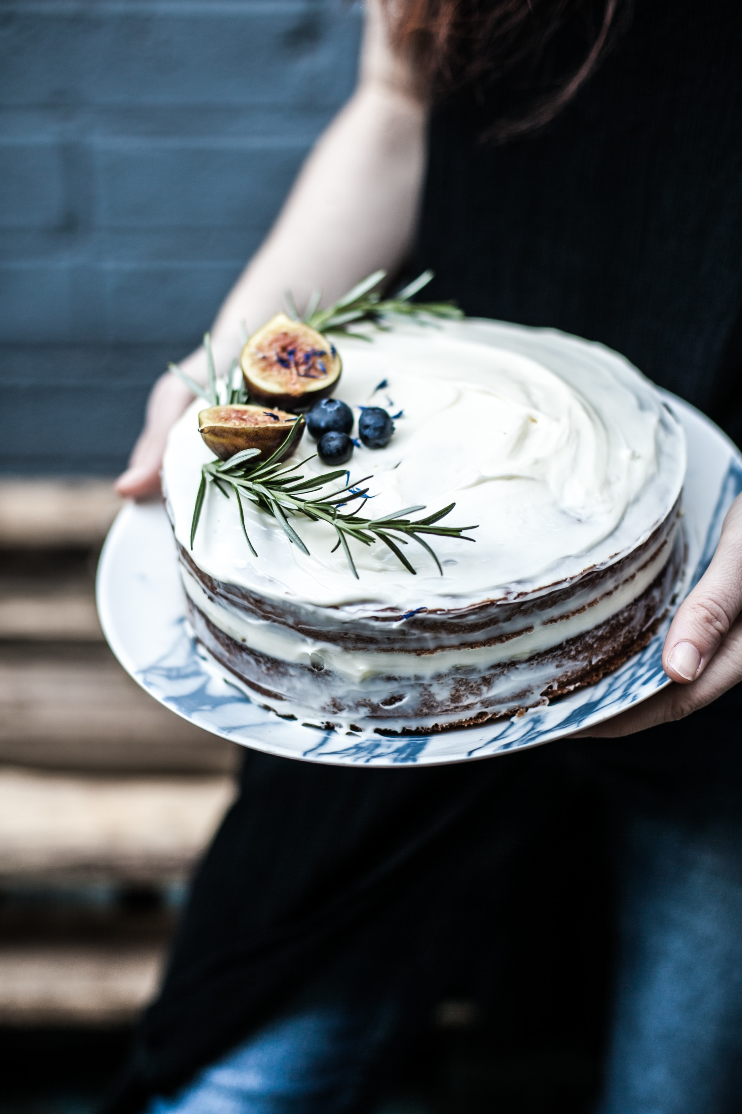 person holding round white icing-covered cake with blue berry on top