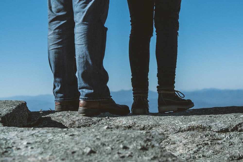 two person wearing jeans standing beside each other