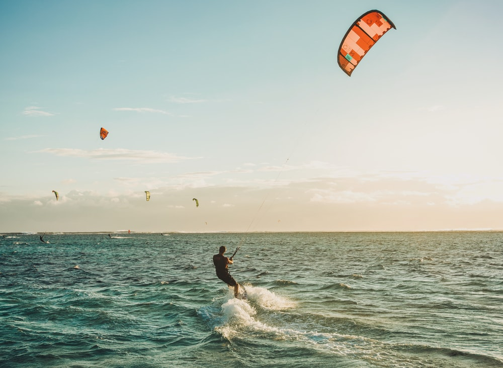person parasailing on body of water under blue sky during daytime