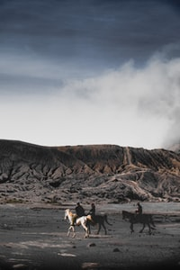 three person riding on horse near mountain under white clouds