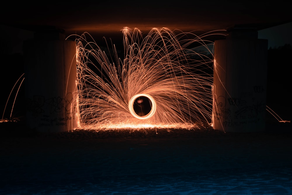 steel wool photography of person under arch