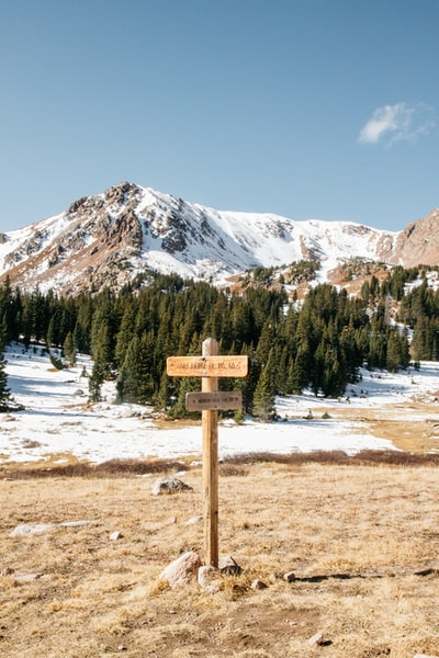 wooden signage stand on the ground and view of snow mountain