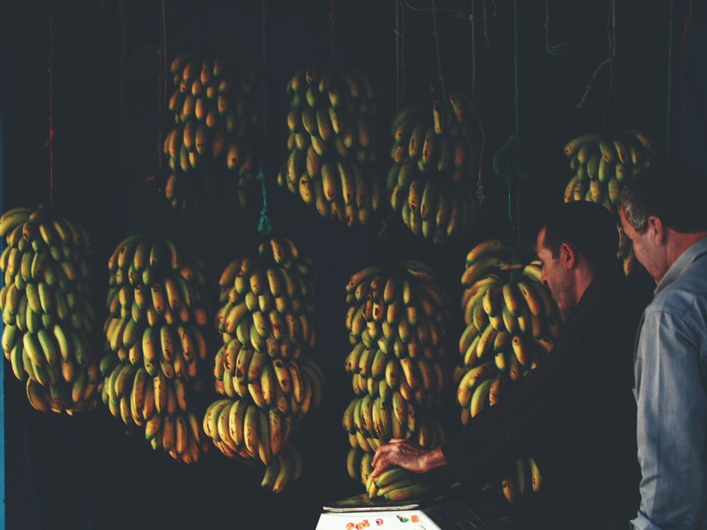 man putting banana on scale