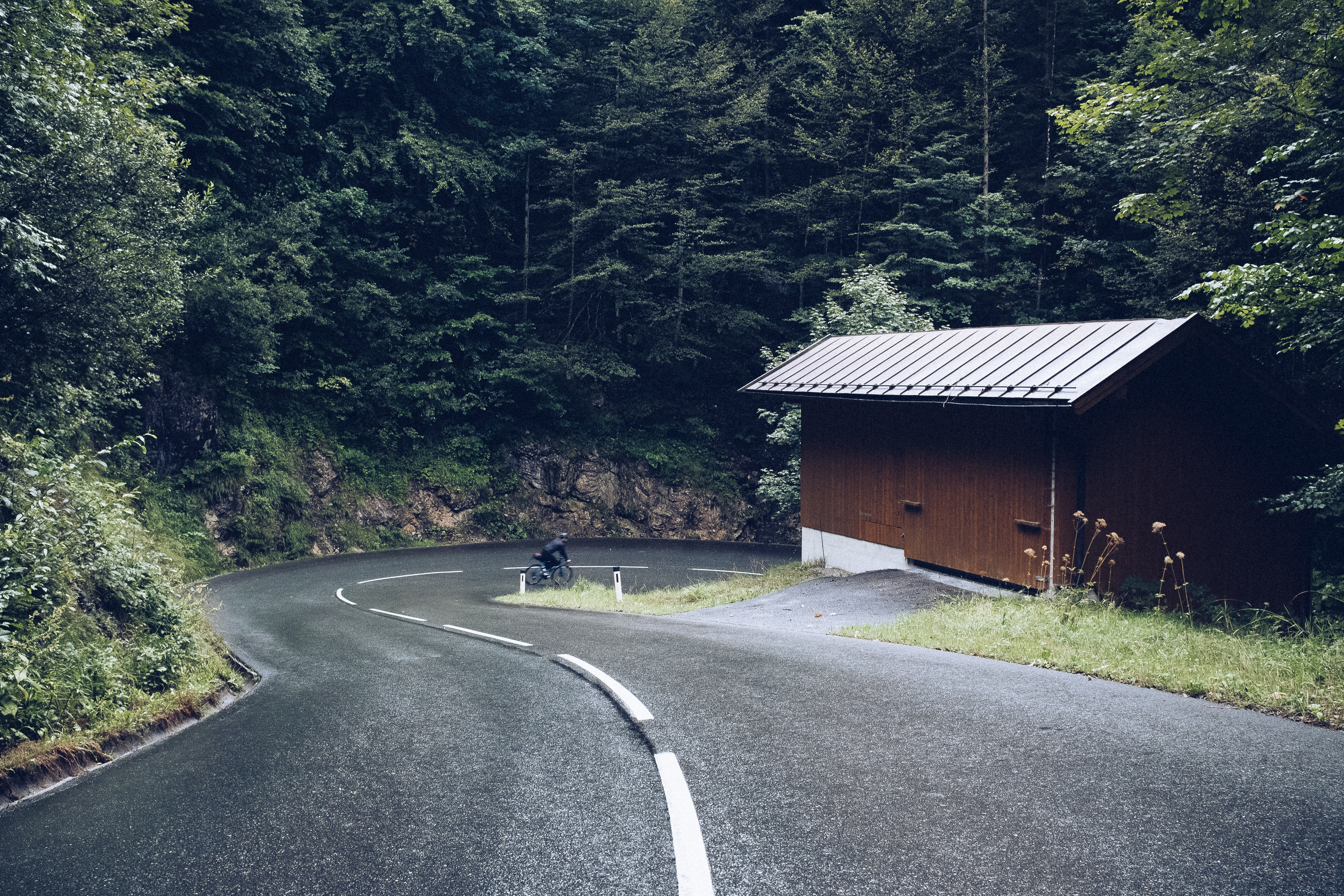 brown wooden house beside asphalt road surrounded with trees at daytime