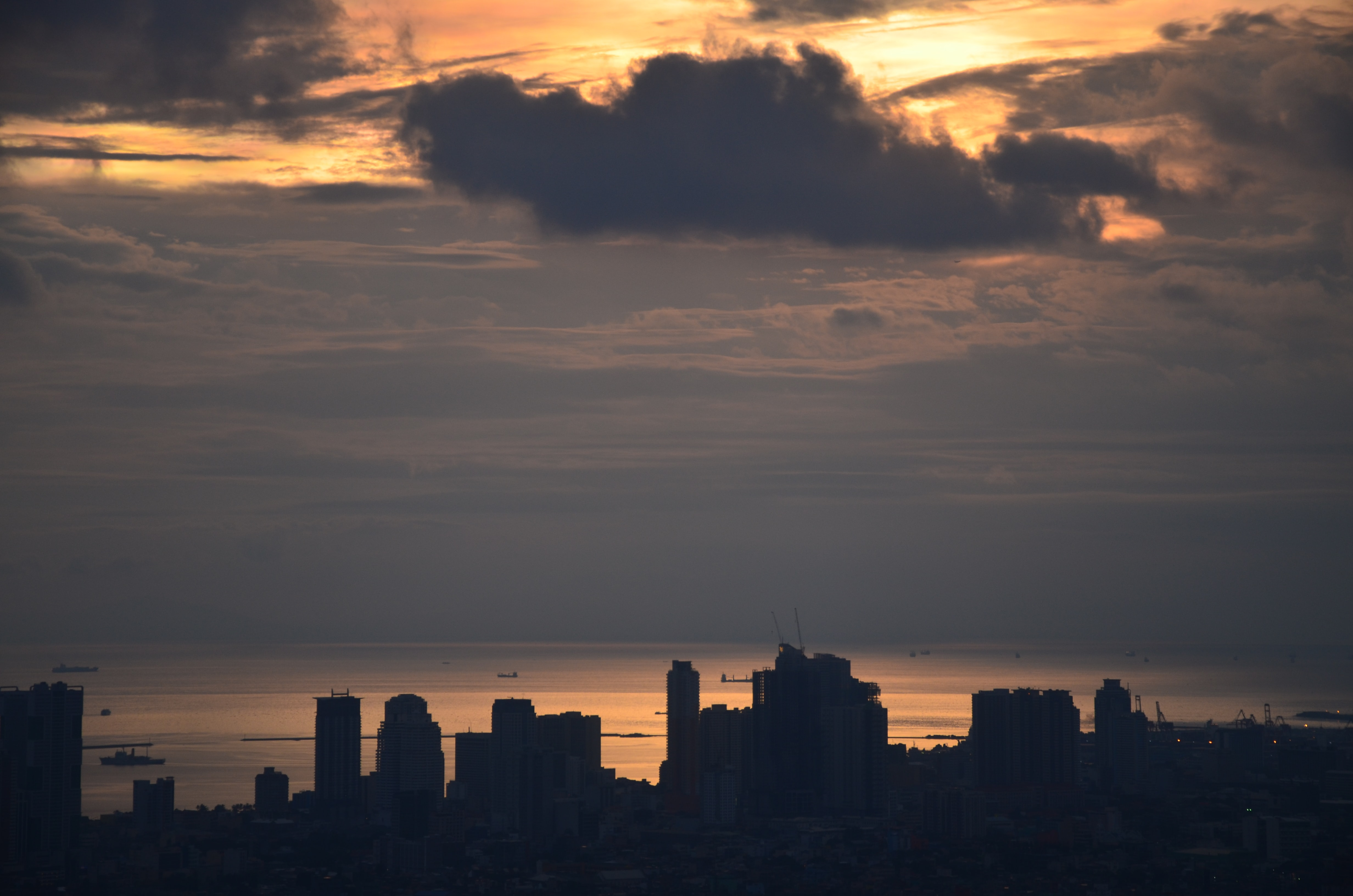 silhouette of buildings under gray clouds during golden hour
