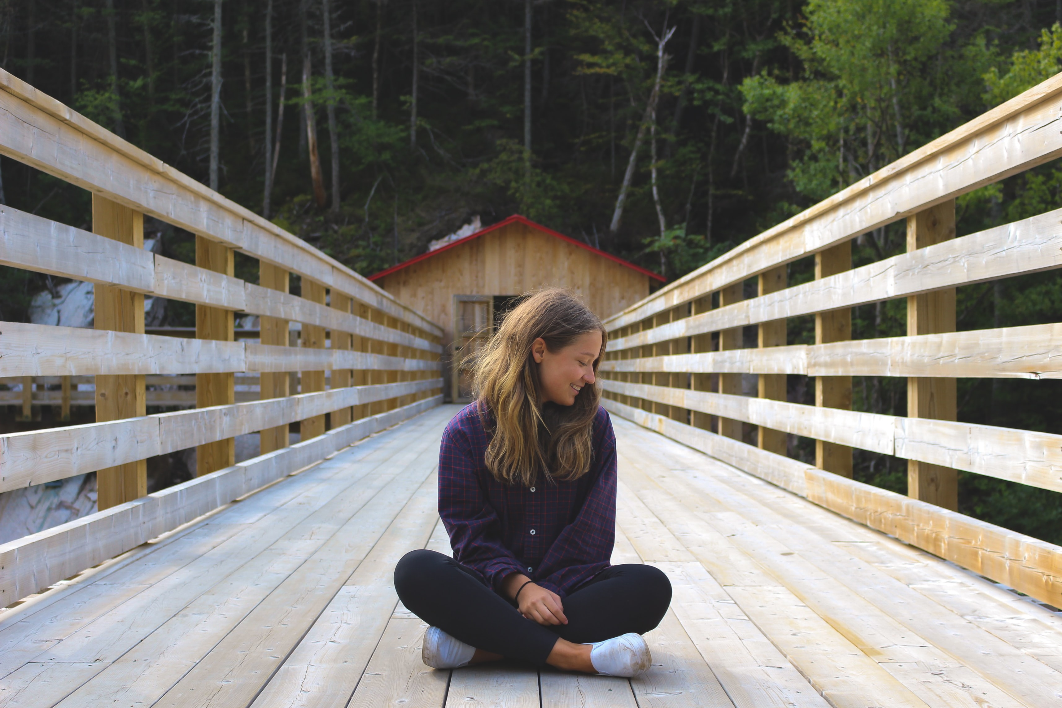 woman sitting on wooden bridge near forest