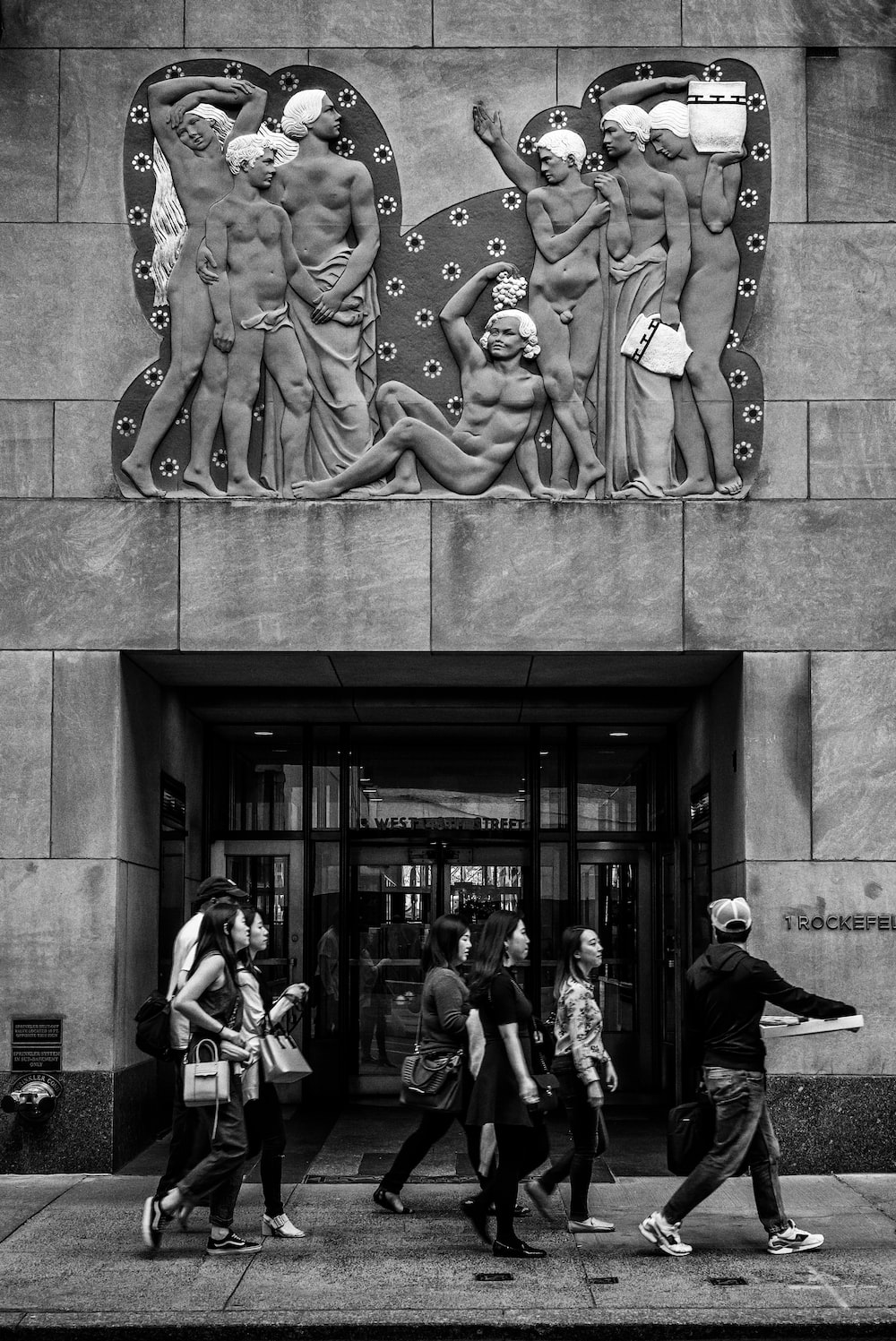 grayscale photography of people walking under sculpted wall