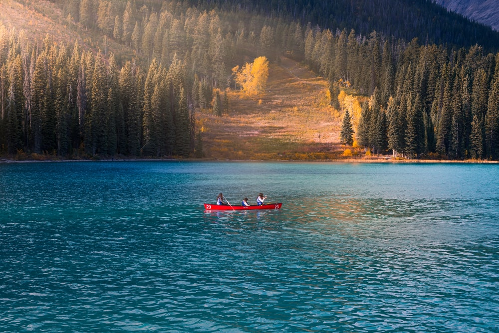 three person in red rowboat on blue calm body of water at daytime