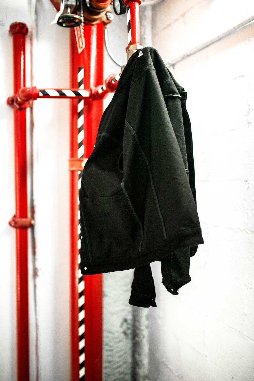 black coat hanging on red coat raack
