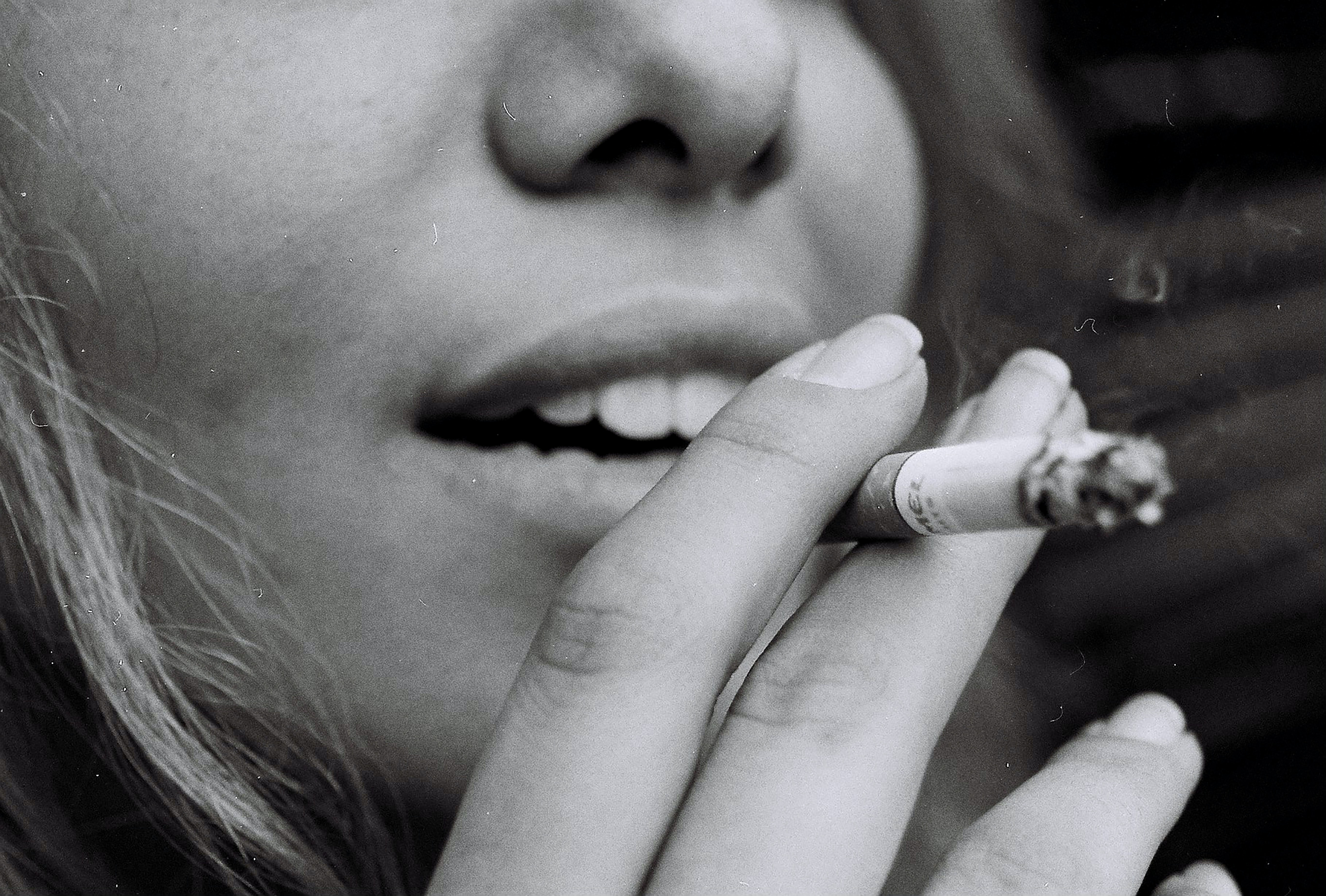greyscale photo of woman smoking cigarette