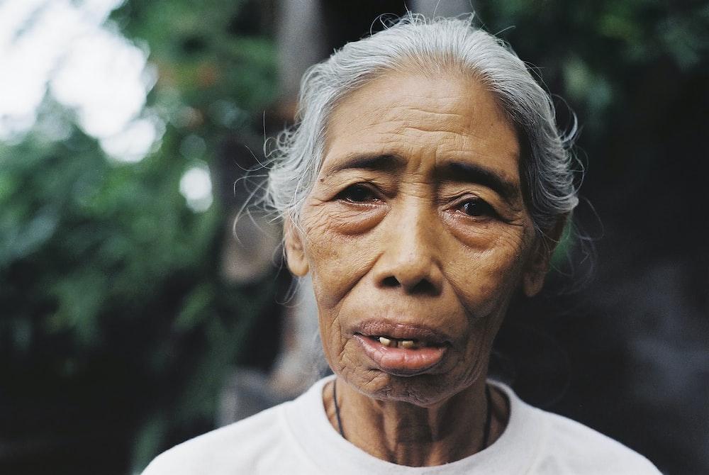 macro photo of woman in white crew-neck top