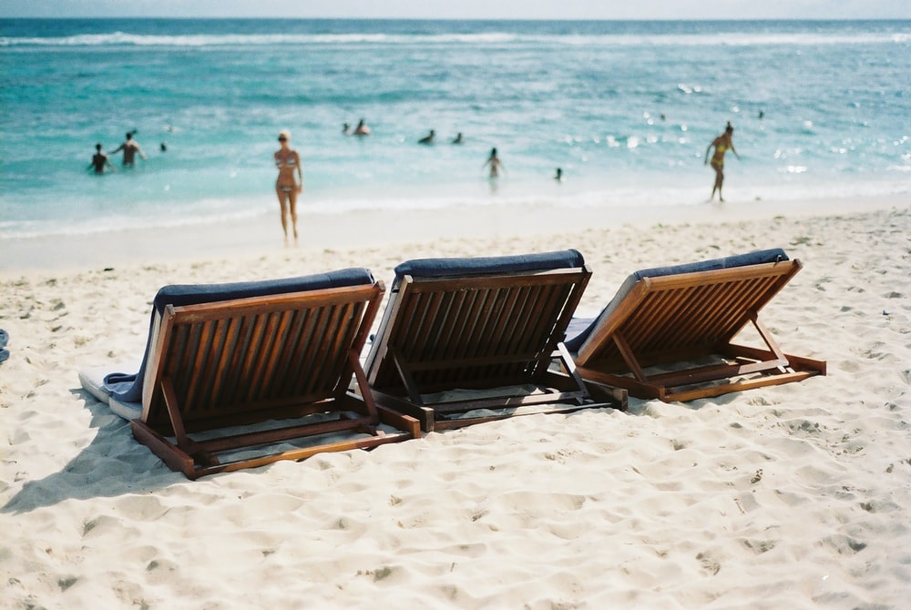 three sun loungers on seashore near woman in bikini
