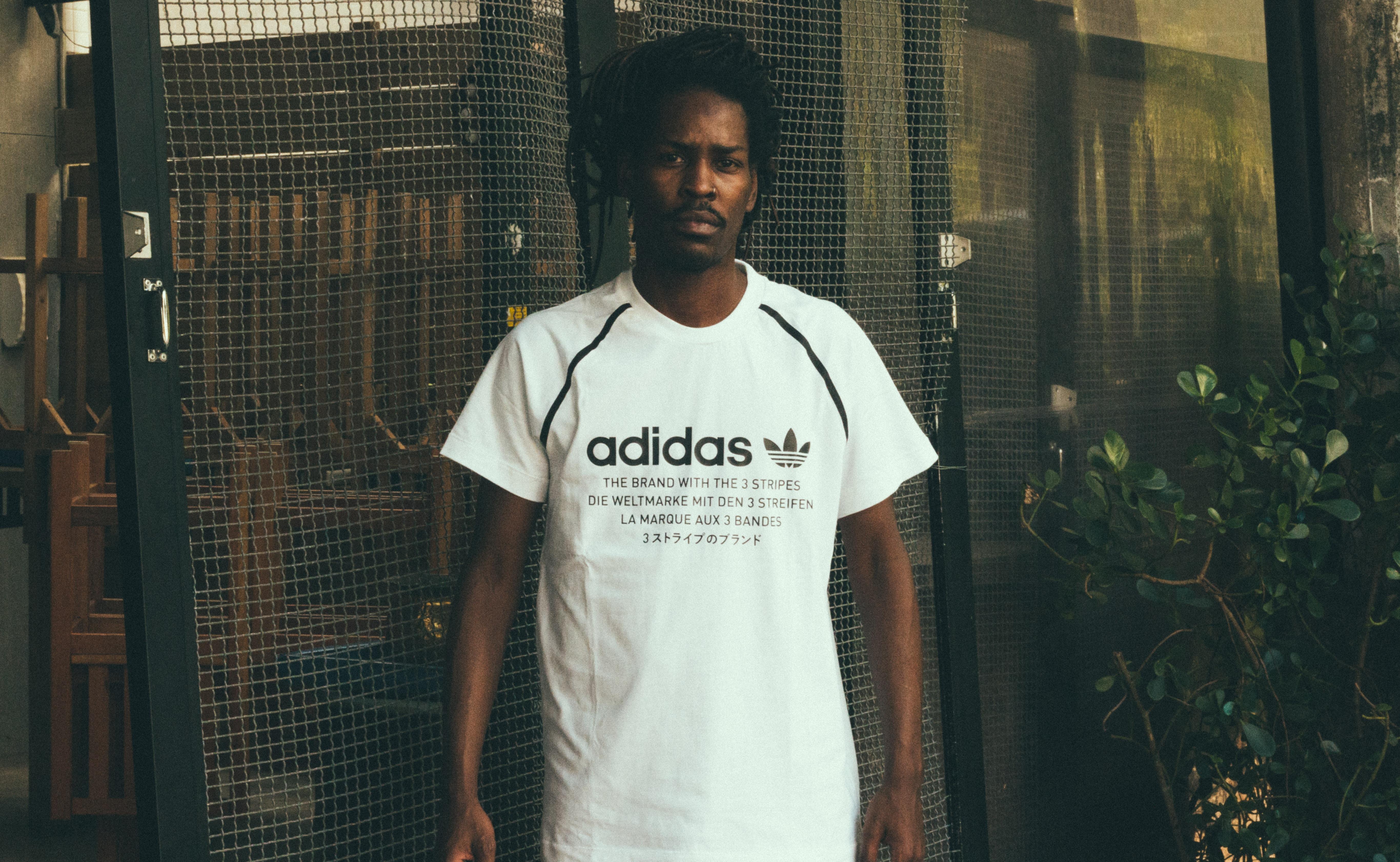 man wearing white and black adidas crew-neck t-shirt