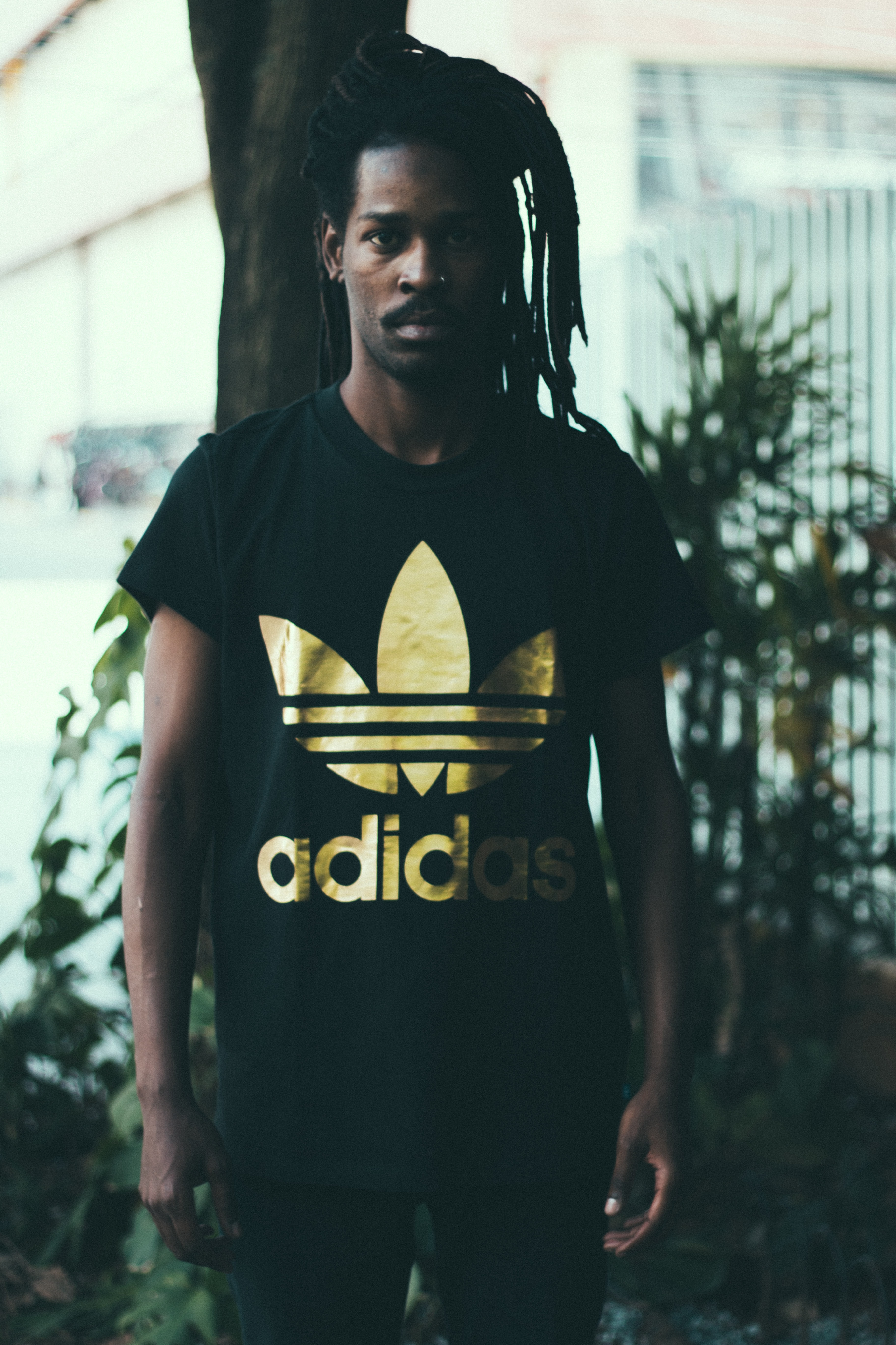 depth of field photography of man wearing black and gold adidas graphic crew-neck T-shirt standing in front of tree