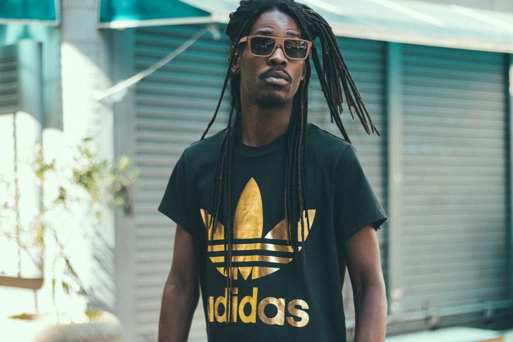 man with dreadlocks hair wearing black and gold Adidas crew-neck shirt