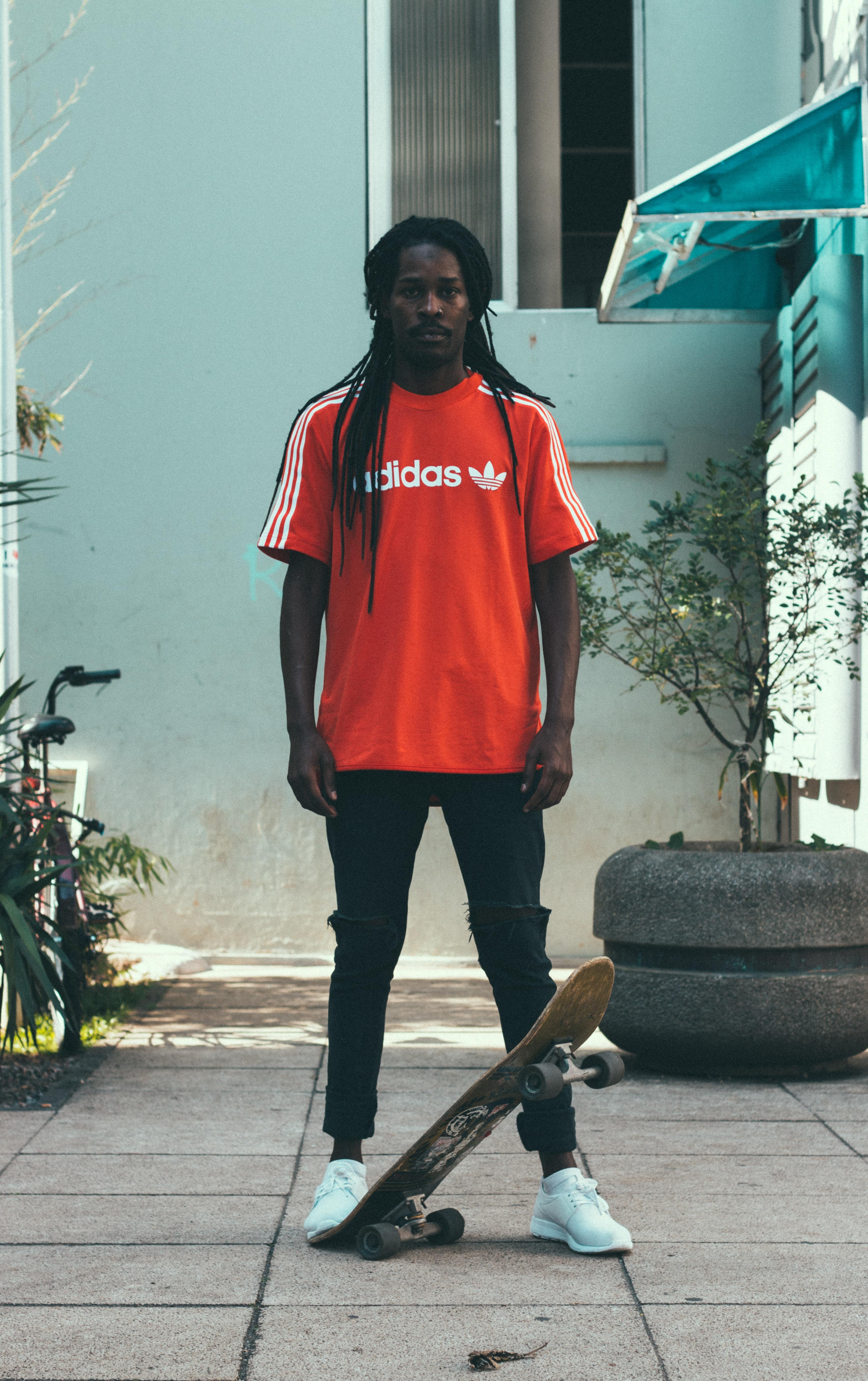 man standing near gray garden pot with skateboard