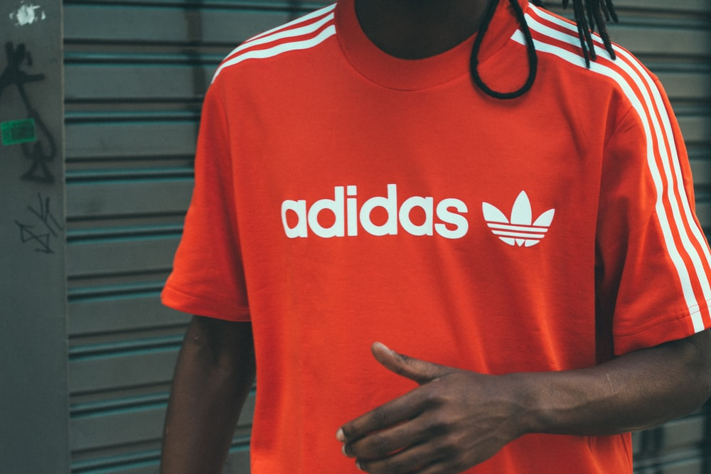man wearing red and white adidas crew-neck T-shirt