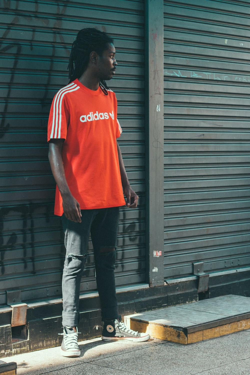 man wearing red Adidas t-shirt in front of roller shutter