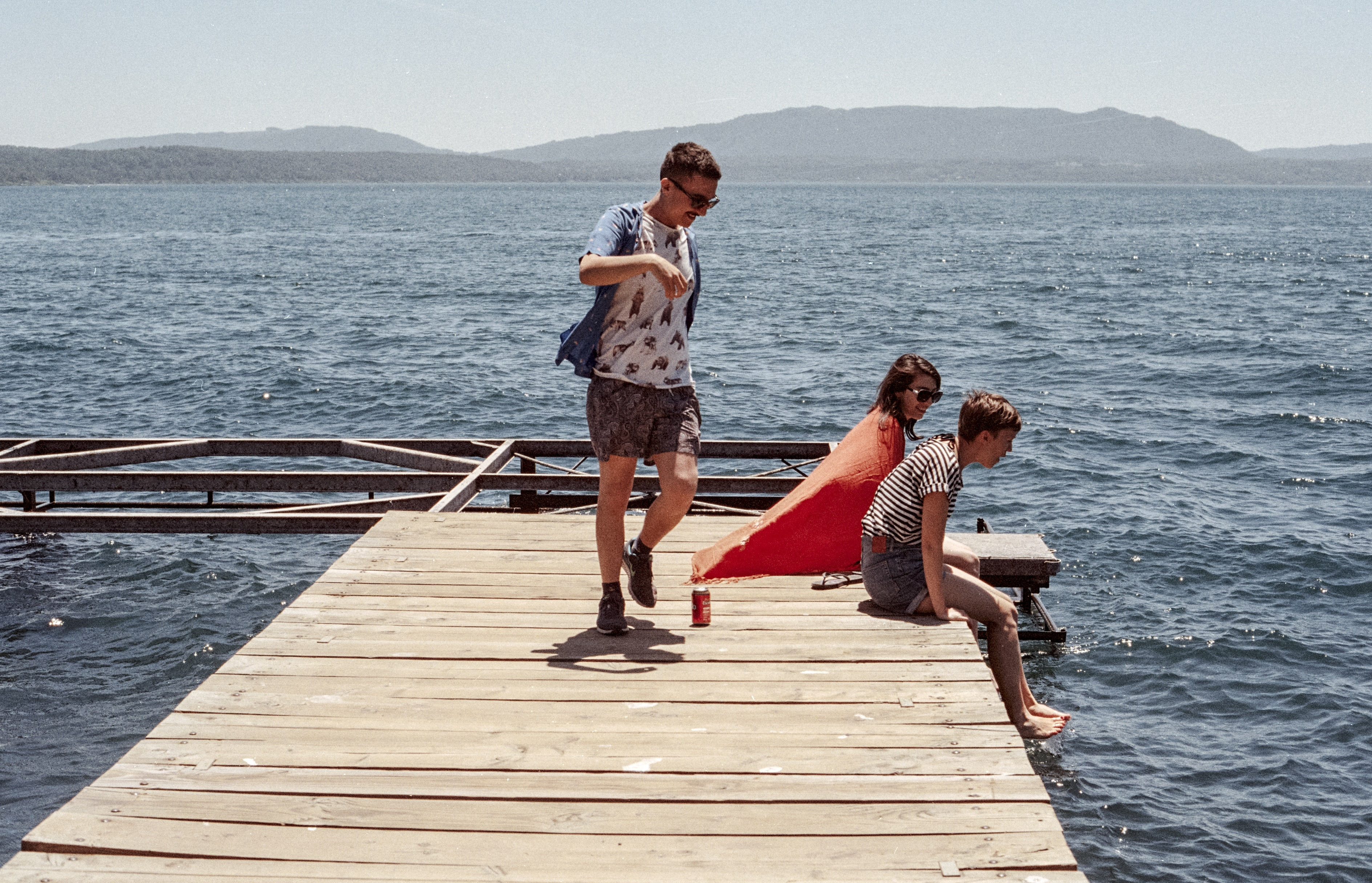 three person standing on dock