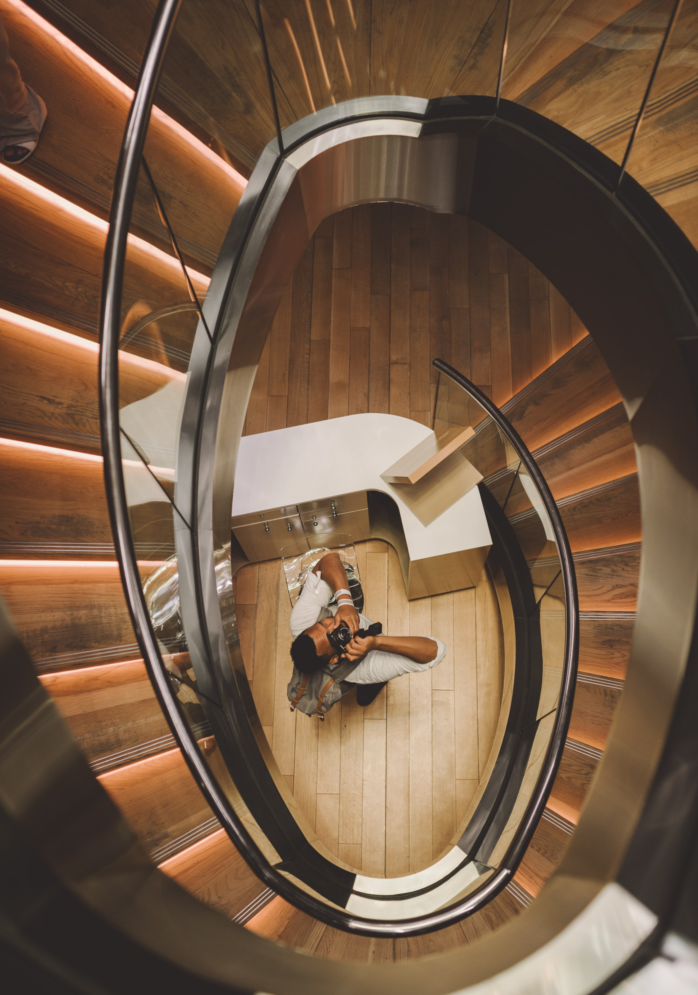 aerial photography of man holding camera taking picture under spiral stair