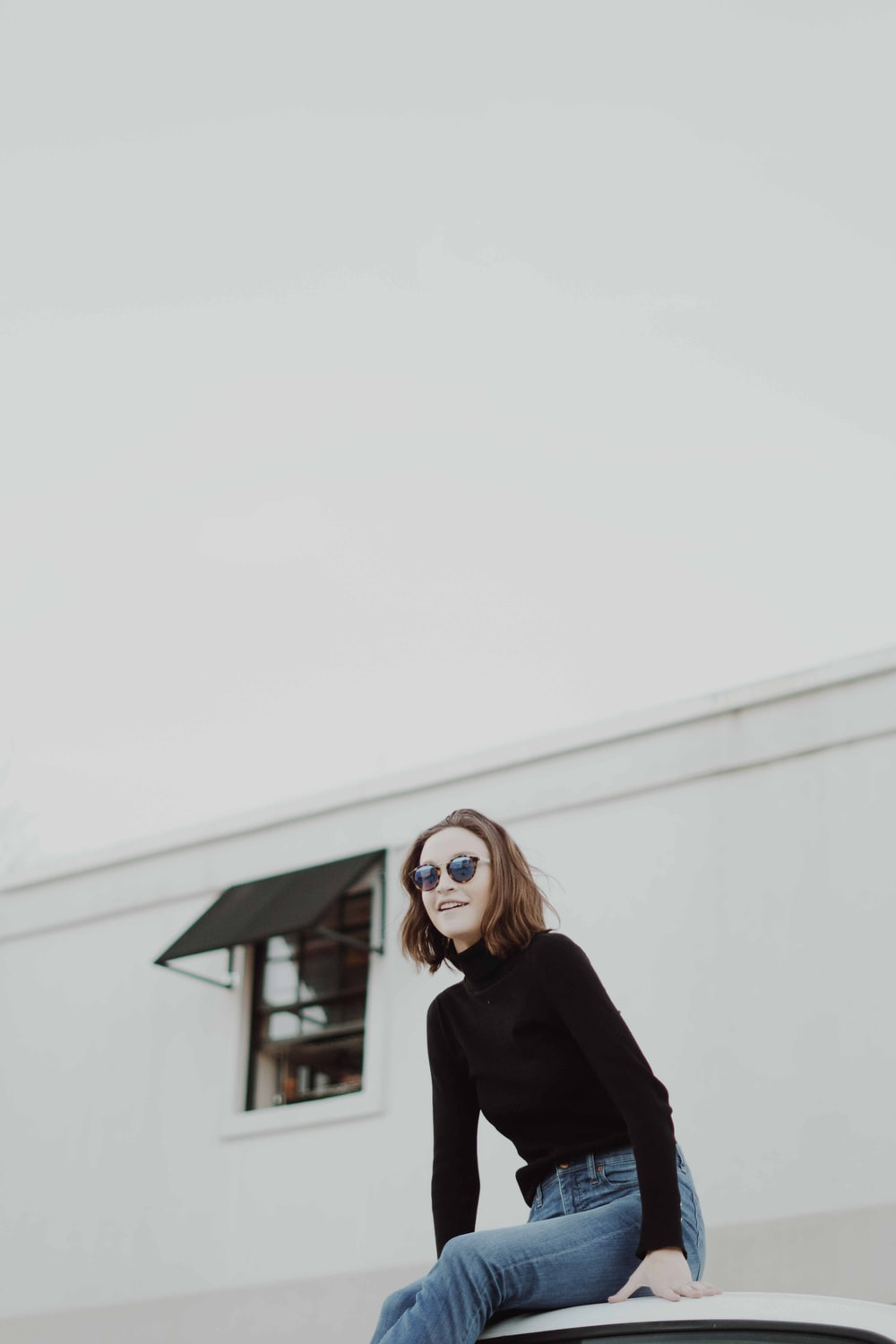 woman in black sweatshirt in front of white building
