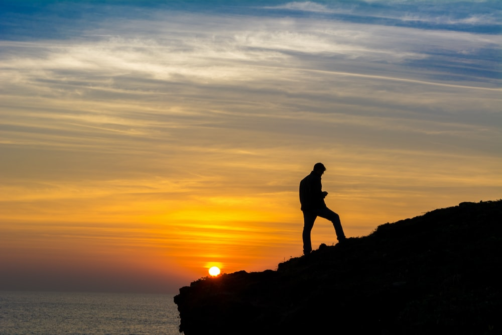 sihouette of person standing on rock formation during golden hour