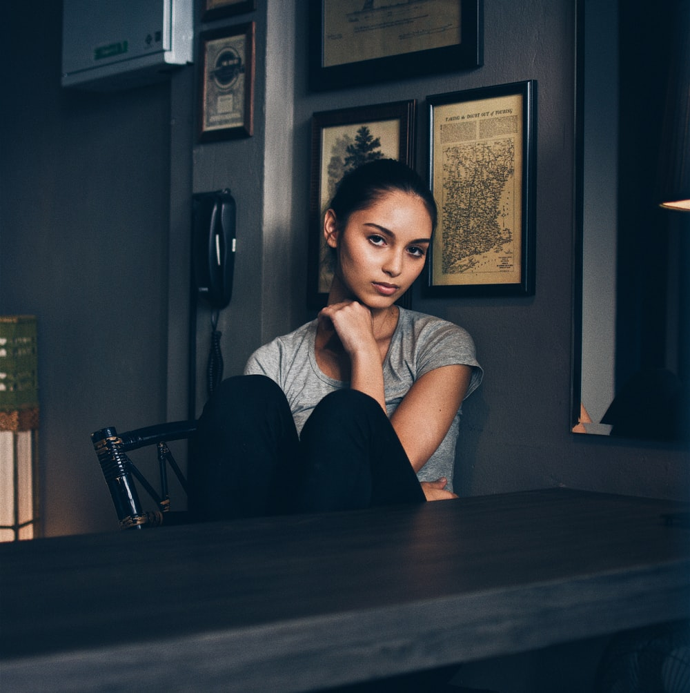 woman sitting on chair infront of empty table