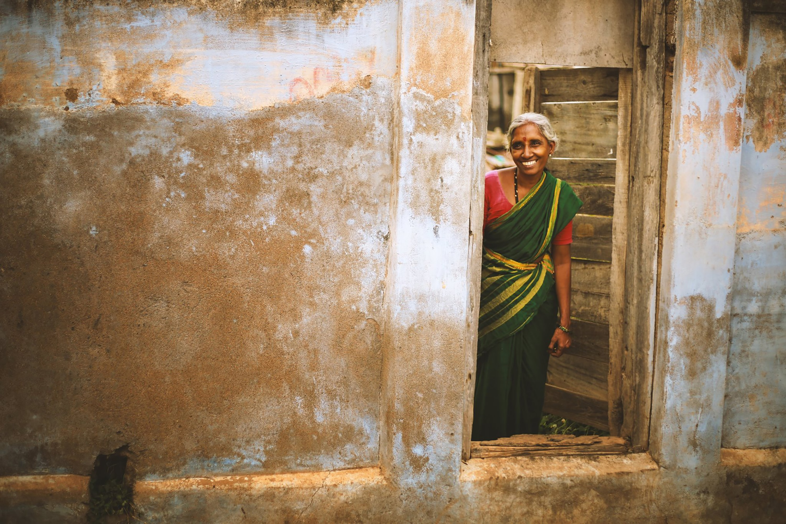 smiling woman wearing sari standing near door