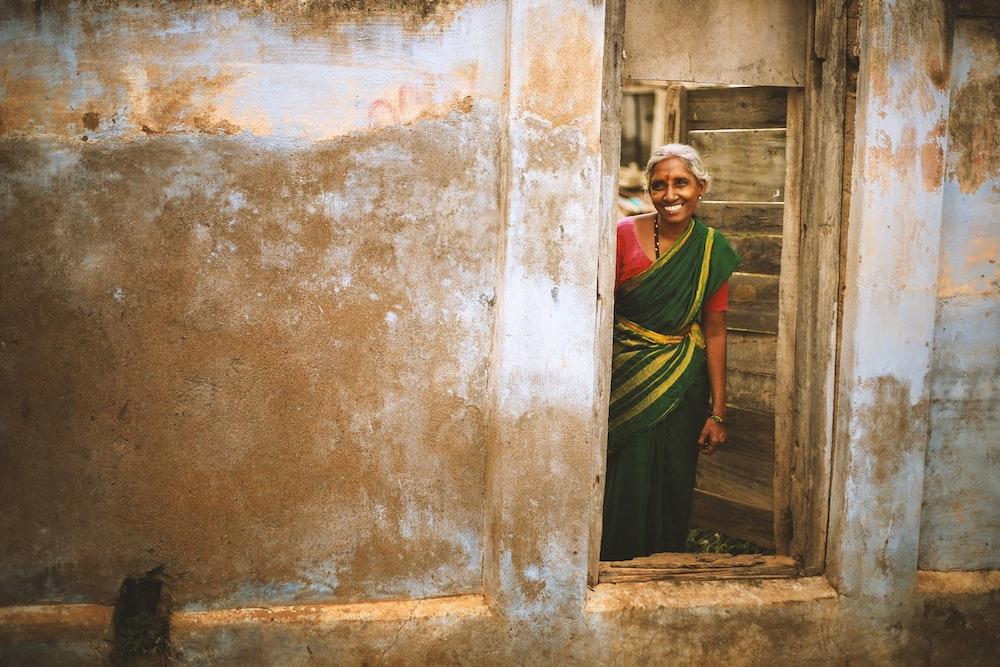 smiling woman wearing sari standing near door