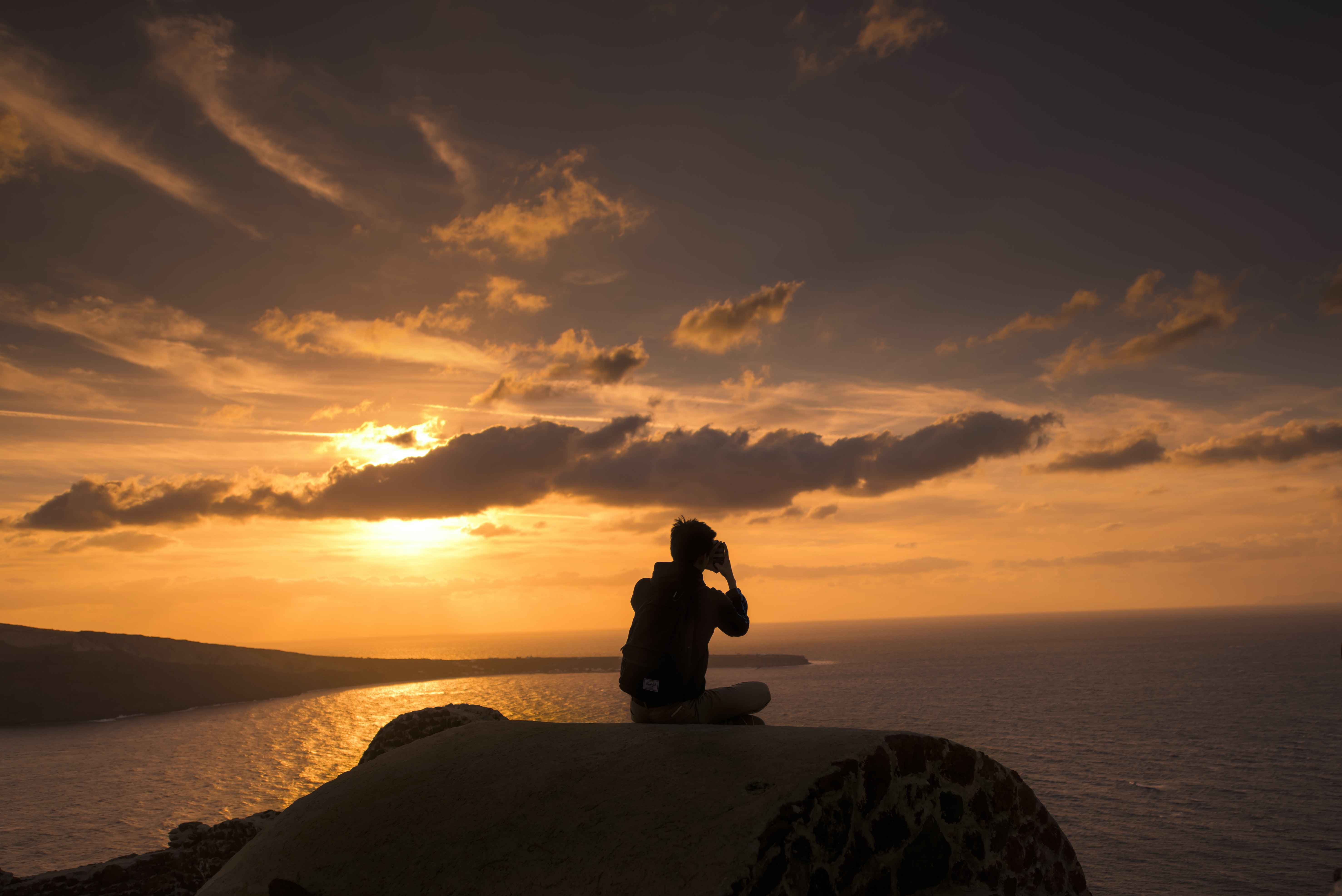 silhouette of person sitting on hill near body of water
