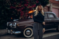 woman posing for photo standing in front of vintage car during daytime